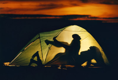Couple engaging in sex in tent, silhouette, sunset
